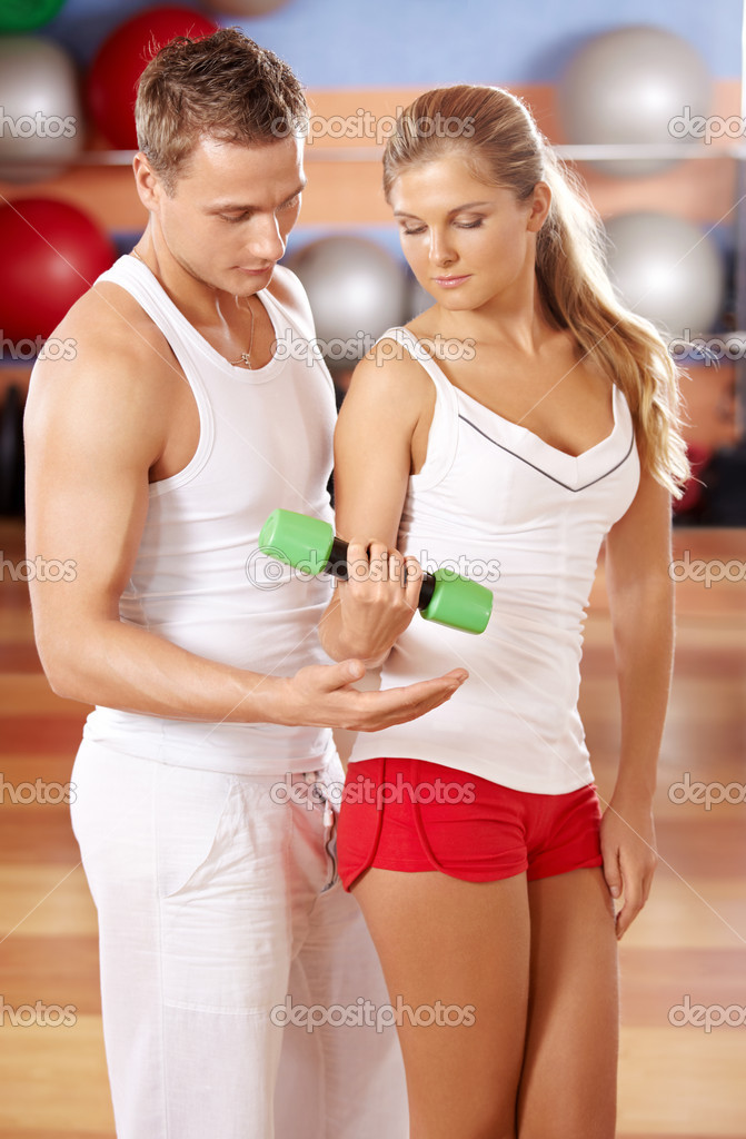The trainer instructs the girl from dumbbells  Stock Photo #4016264