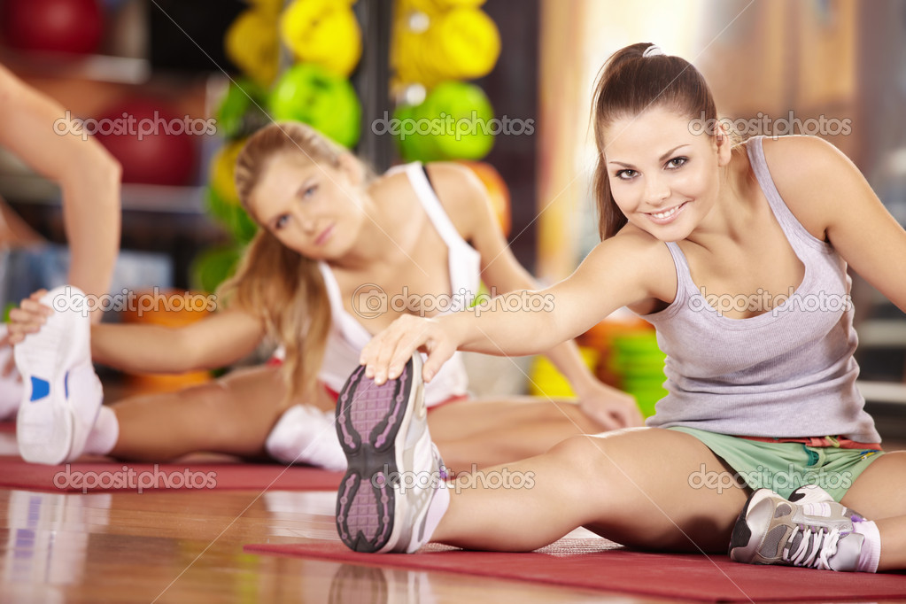 Two smiling girls do exercise in sports club — Stok fotoğraf #4016314