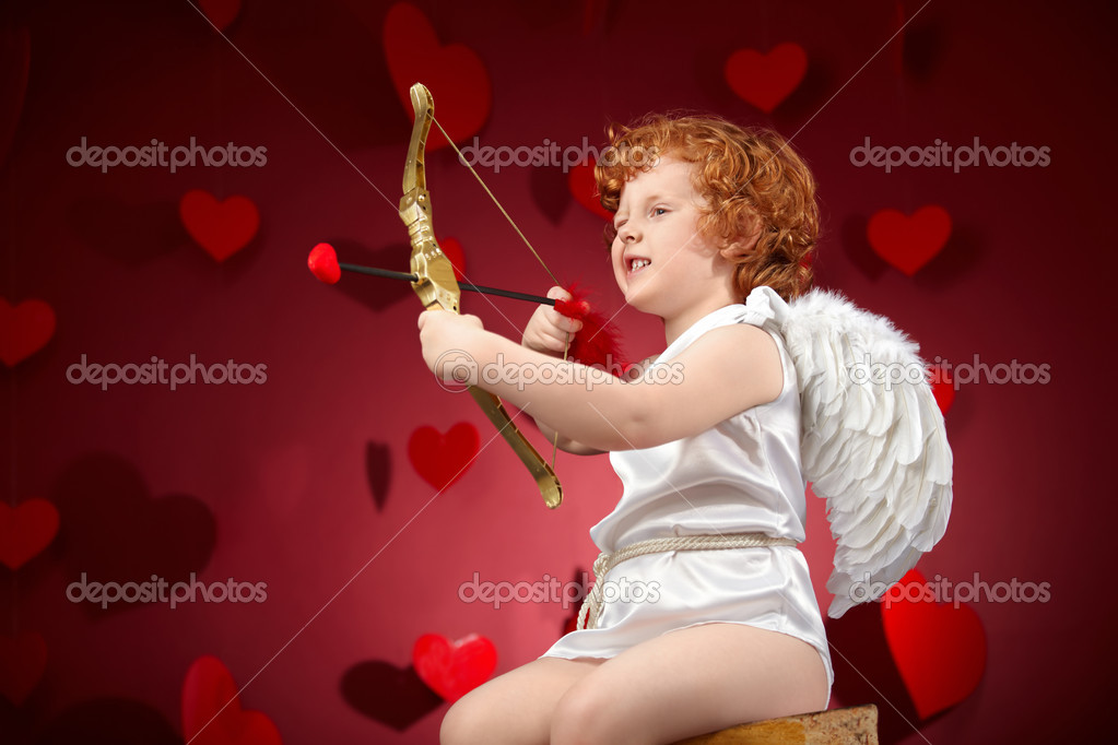 Little boy in an image of the cupid on a red background — Stock Photo #4016534