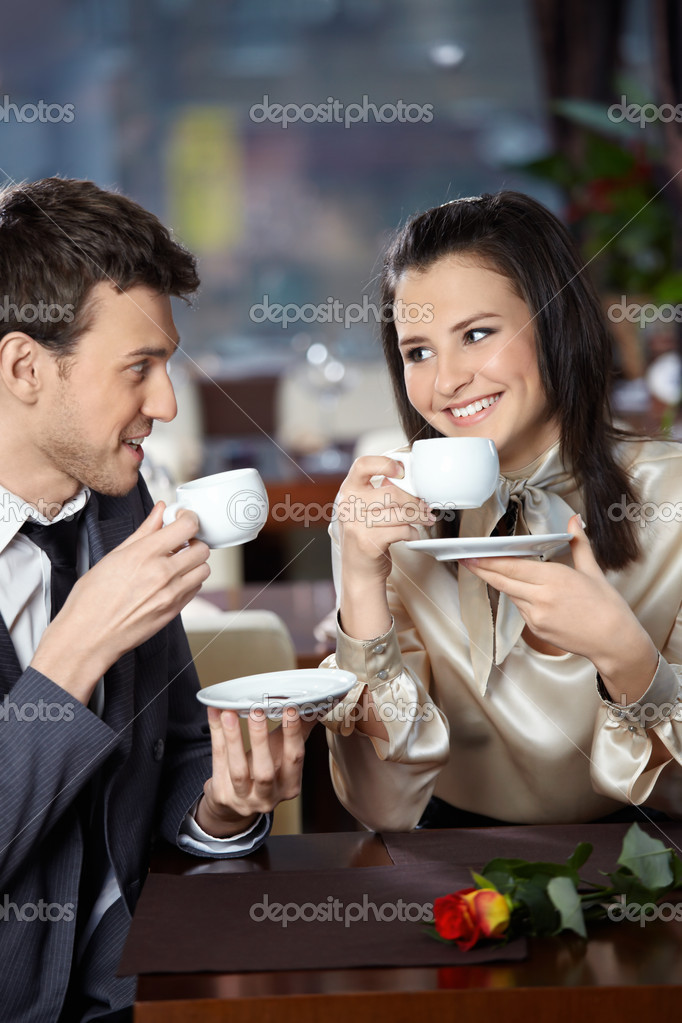Happy smiling couple in cafe with cups in hands — Stock Photo #4019137