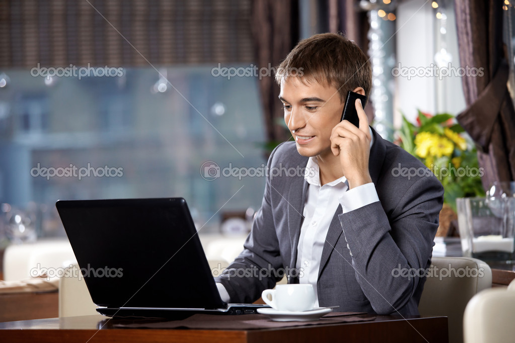Business man with the laptop uses a mobile communication in cafe — Stock Photo #4019317