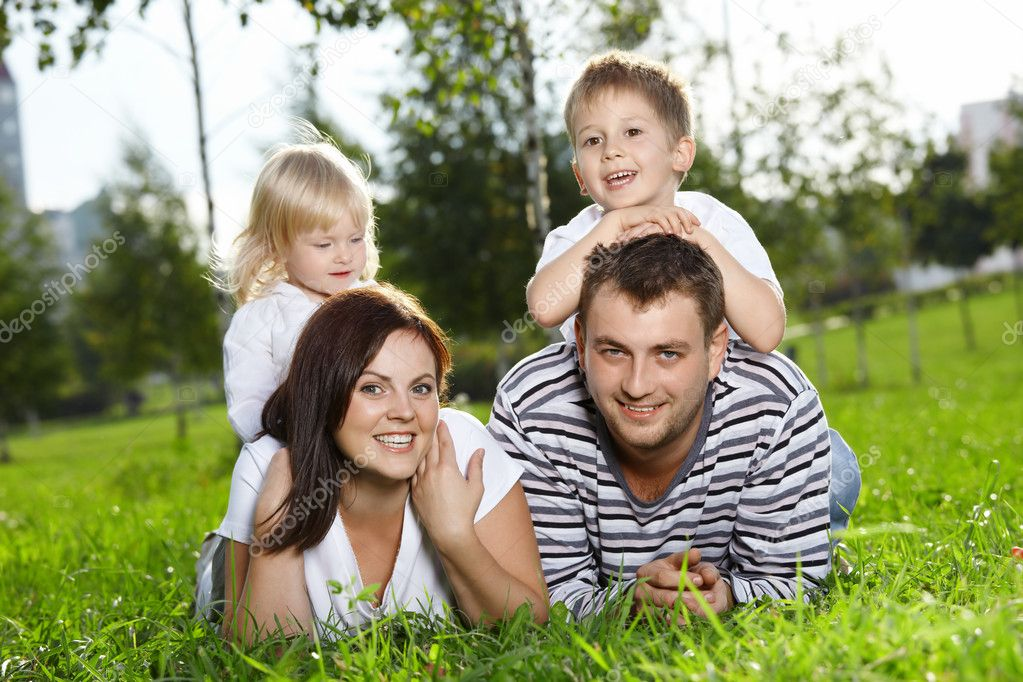 Happy family from four persons lies on a summer lawn — Stock Photo #4019348