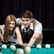 Happy couple in a billiard room — Stock Photo