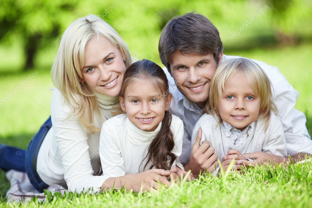 Young parents with children on the grass — Stock Photo #4247961