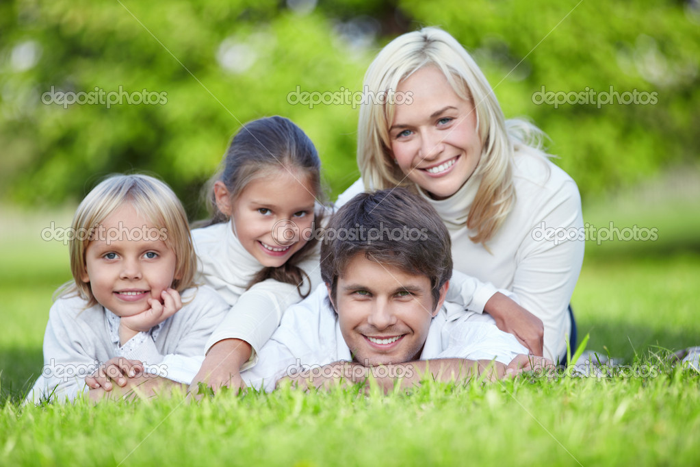 A happy family lying on the grass in the park — Stock Photo #4247973