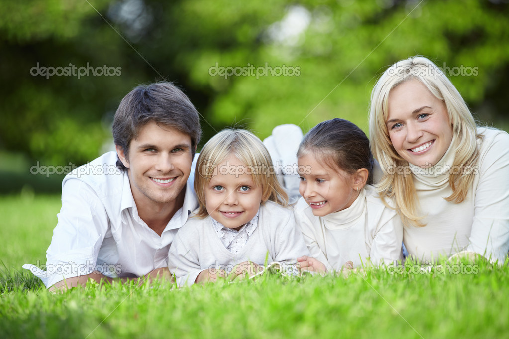 Young families with children lying on the grass in the park — Stock Photo #4247987