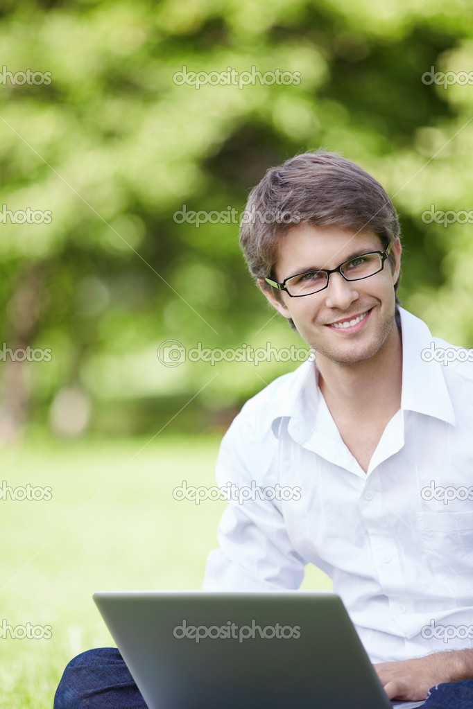 A smiling young man with laptop outdoor — Stock Photo #4248043