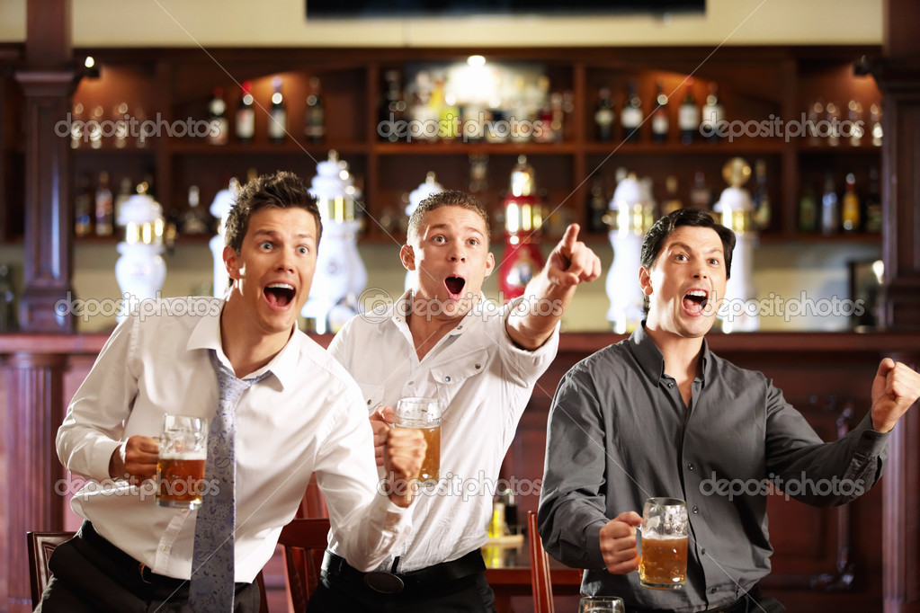 Three men with beer rejoice the victory of their favorite team in the pub — Stock Photo #4248318