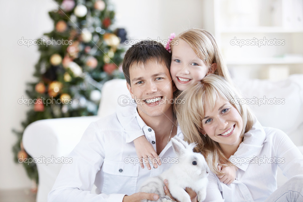 A happy family with a rabbit at home — Stock Photo #4270489