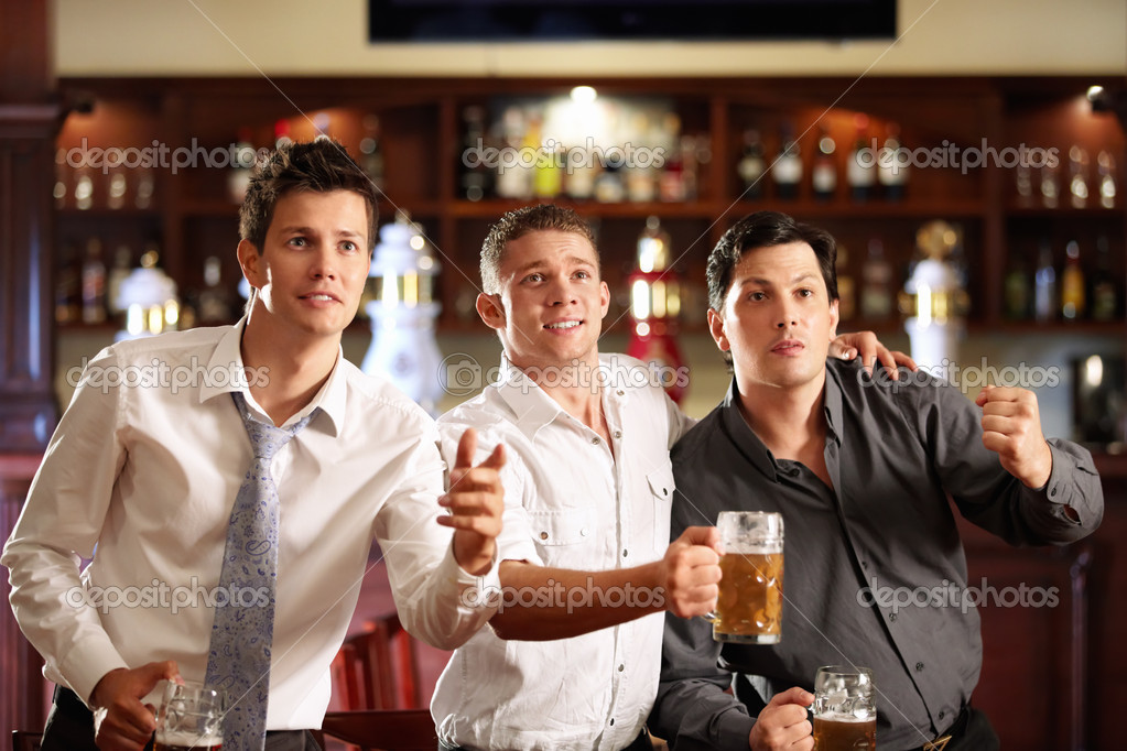 Young men with a beer watching the match in the bar  Stock Photo #4270969