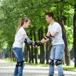 The young couple on rollers — Stock Photo