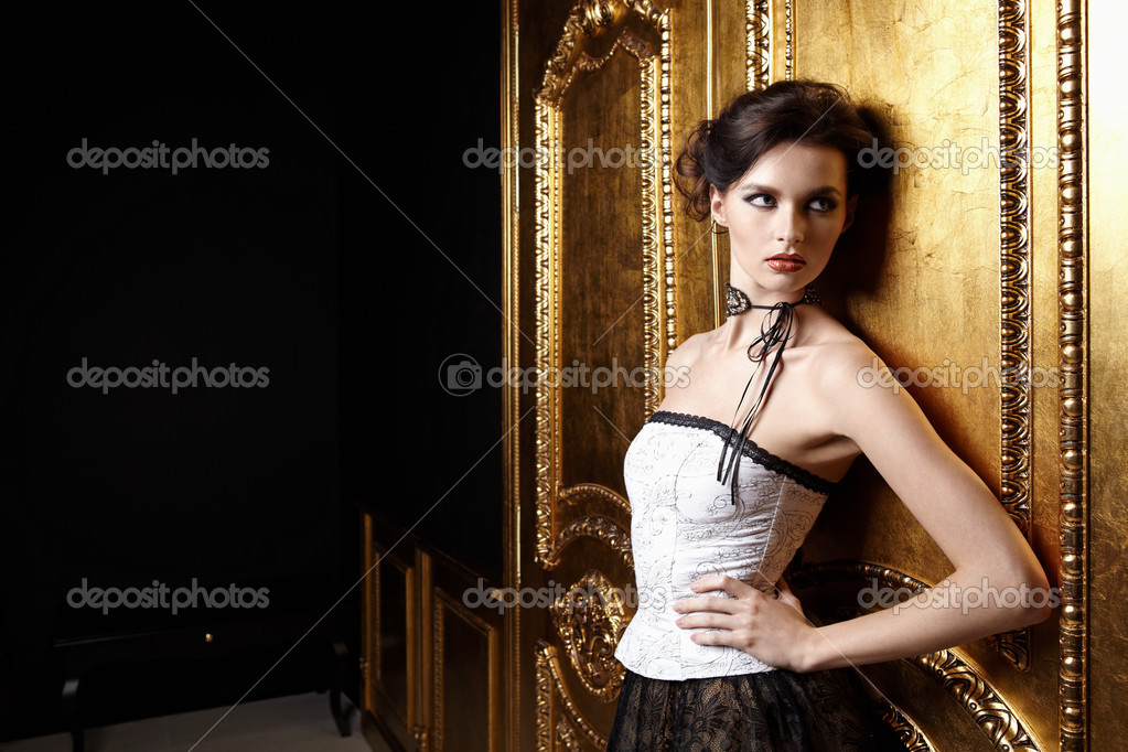 The beautiful girl in a dress at a gold door  Stock Photo #4512080
