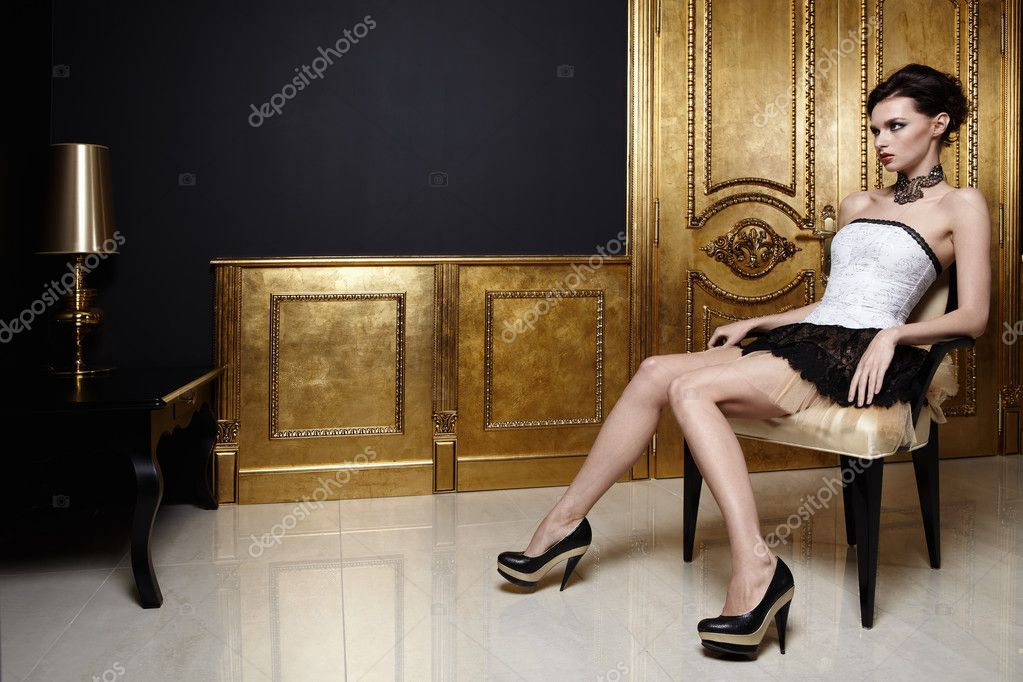 The beautiful girl sits in an armchair in a magnificent interior — Stock Photo #4512103