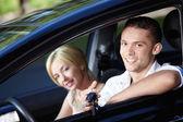 Het gelukkige paar in de auto — Stockfoto