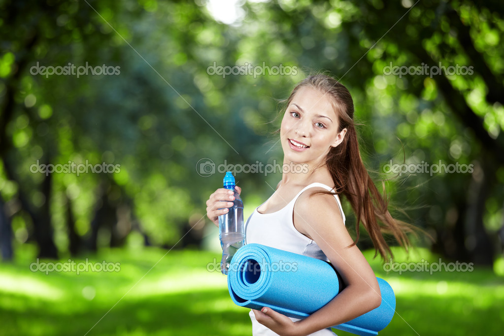 Girl with a bottle of water and gymnastic mats turn  Stock Photo #4593706