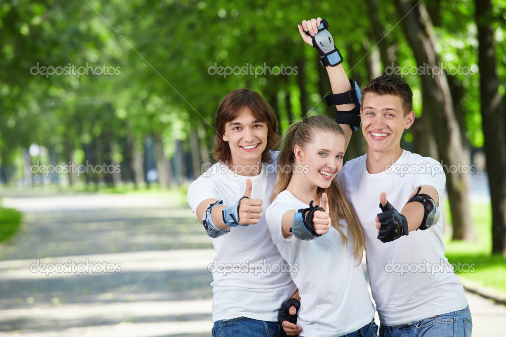 Three young in equipment show a thumb upwards — Stock Photo #4593749