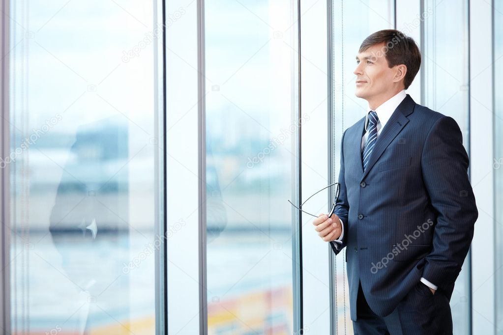 A man in a business suit looks out the window — Stock Photo #4593956