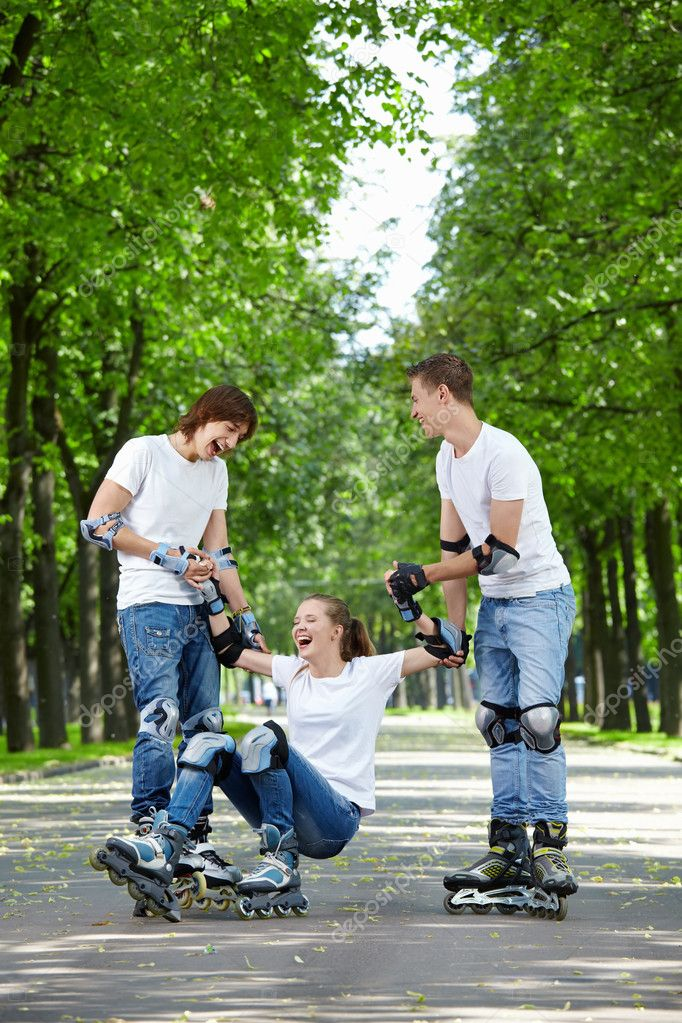 Young guys raise the fallen girl on roller skates — Stock Photo #4593979
