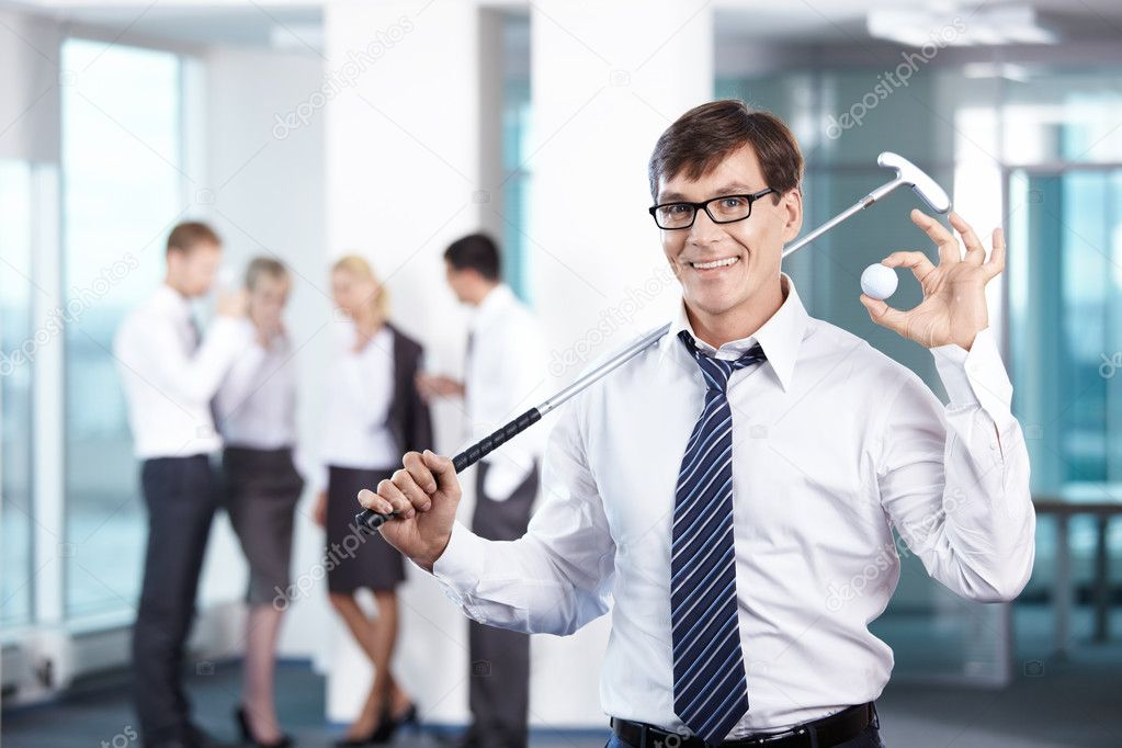 Businessman with a golf club against the staff office — Stock Photo #4594231