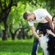 Stock Photo: A young couple walking a dog