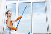Nice girl washing a window — Stock Photo
