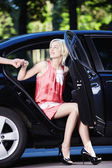 A beautiful girl comes out of the car — Stockfoto