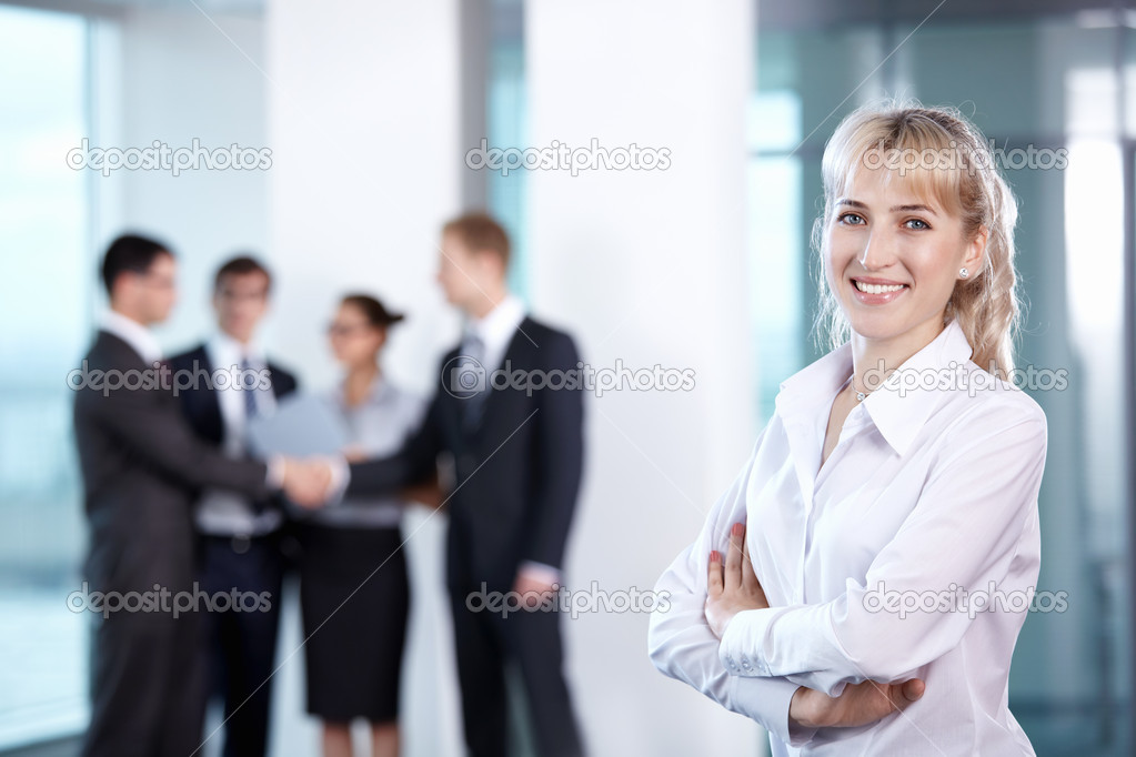 Businesswoman in office on the background of serving staff — Stock Photo #4604871