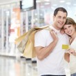 Couple in store with a credit card — Stock Photo