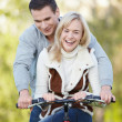 Young attractive couple rides a bicycle — Stock Photo