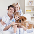 Smiling family with a dog — Stock Photo