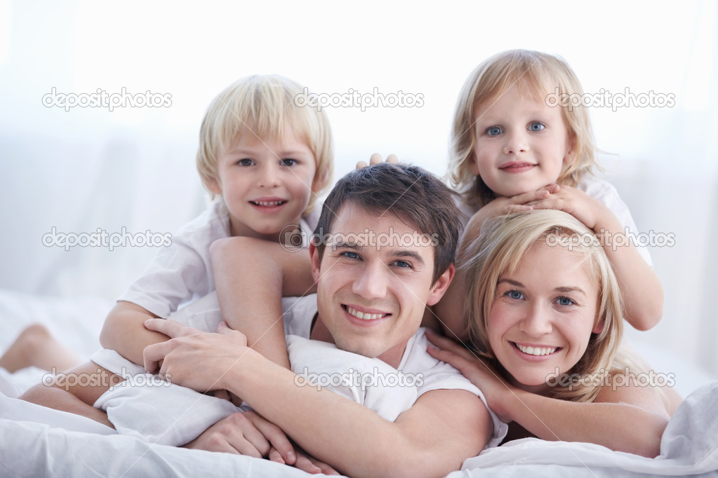 A family with two children on a bed in the bedroom  Stockfoto #4716908