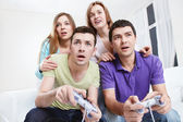 Young friends playing video games — Stock Photo