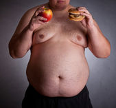 Fat man with burger and apple — Stock Photo