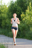Young woman is jogging in the park — Stock Photo
