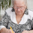 Senor woman signing document — Stock Photo