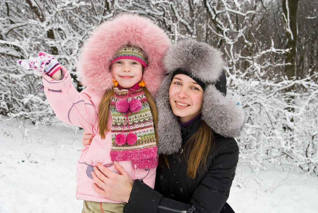 Young mother and daugther in winter clothing in a winter woods — Stock Photo #4478433