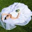 Stock Photo: Bride lying on wedding dress
