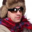 Man in a fur hat with sunglasses — Stock Photo