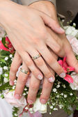 Hands on wedding bouquet — Stock Photo