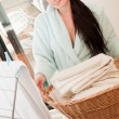 Beautiful woman holding fresh towels in the basket — Stock Photo