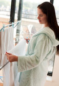 Beautiful woman hanging clothes — Stock Photo