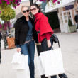 Happy smiling women shopping with white bags — Stok fotoğraf