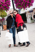 Happy smiling women shopping with white bags — Stock Photo