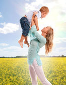 Portrait of happy mother with joyful son over spring flower field — Stock Photo
