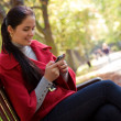 Young Caucasian woman with a cell phone, sitting in a park on a — Stock Photo