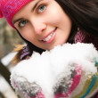 Beautiful young woman outdoor in winter with snow in her hands — Stock Photo