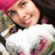Beautiful young woman outdoor in winter with snow in her hands - Stock Photo