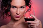 Krásná mladá žena se sklenicí červeného vína — Stock fotografie