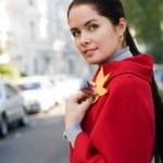 unga kvinnor i röd kappa på gatan — Stockfoto