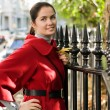 Young women in red coat on the street - Stok fotoğraf